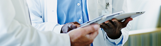 Close up of doctor showing patient someone on tablet