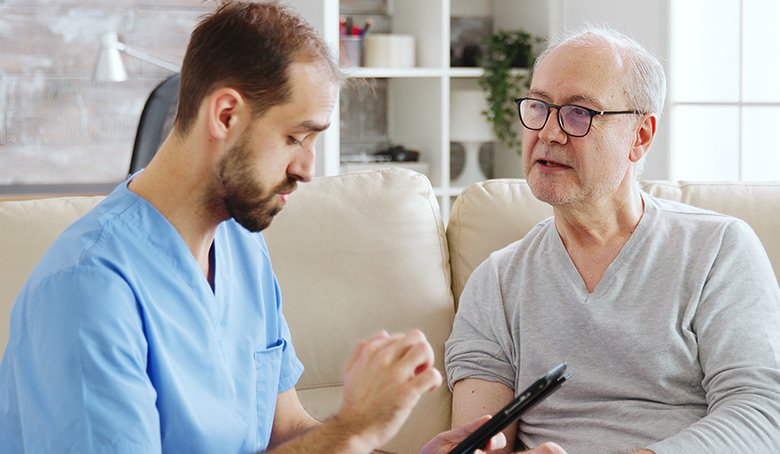 nurse talking with a nursing home patient about his health. The nurse is making notes on a digital tablet
