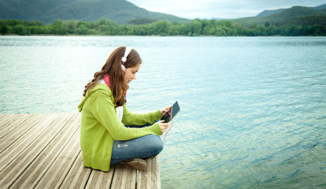girl listening to an audiobook by a lake