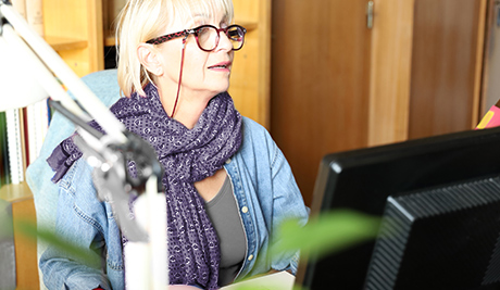 A librarian wearing a purple scarf on her computer.