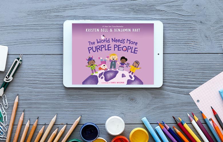 desk with colored pencils and tablet showcasing the book title The World Needs More Purple People