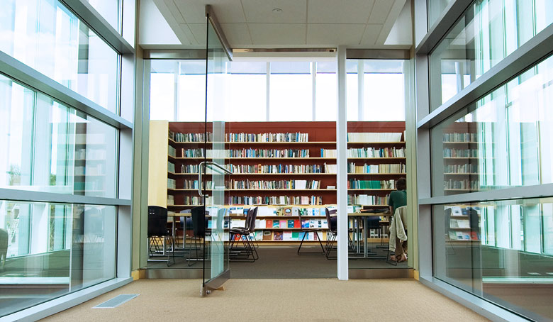 View into a public library from the main hallway. Can see bookcases along the back wall. Bookcases and tables are more in the foreground.