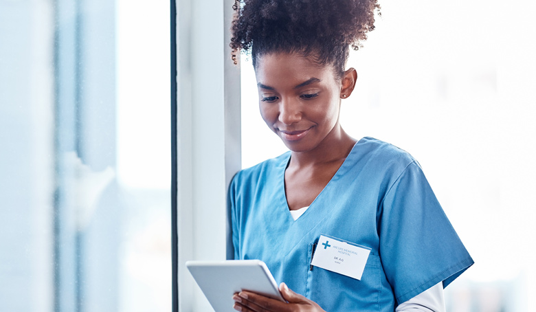 Nurse in scrubs working on tablet against window