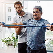 Physical therapist helping a mature male stretch a band in his hands