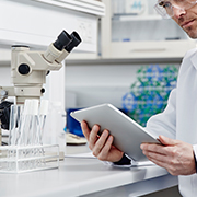 Close up of researcher on tablet in lab setting