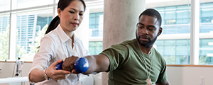 Male with injury uses a hand weight during a physical therapy session. A female physical therapist is helping him with an exercise.